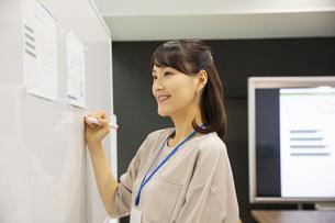 ホワイトボードに書く日本人ビジネス女性の写真素材 [FYI04087472]