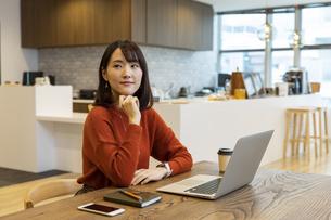 オフィスで遠くを見る日本人ビジネス女性の写真素材 [FYI04087489]