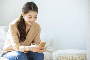 スマートフォンを操作する日本人女性の写真素材 [FYI04087506]