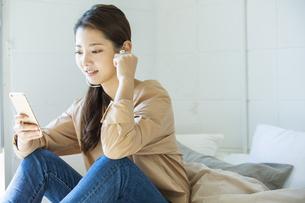 スマートフォンで音楽を聴く日本人女性の写真素材 [FYI04087512]