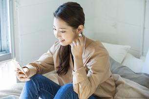 スマートフォンで音楽を聴く日本人女性の写真素材 [FYI04087513]