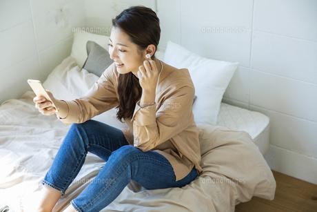 スマートフォンで音楽を聴く日本人女性の写真素材 [FYI04087514]