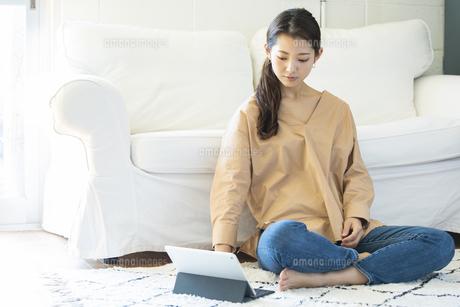 タブレットPCを操作する日本人女性の写真素材 [FYI04087517]