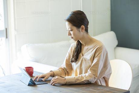 タブレットPCを操作する日本人女性の写真素材 [FYI04087518]