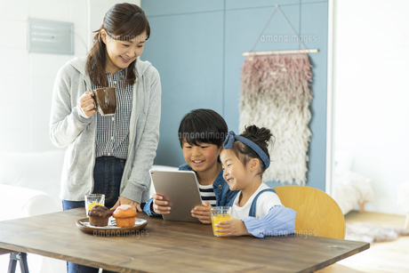 タブレットPCを見る日本人親子3人の写真素材 [FYI04087526]