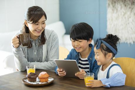 タブレットPCを見る日本人親子3人の写真素材 [FYI04087527]