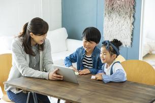 タブレットPCを見る日本人親子3人の写真素材 [FYI04087528]