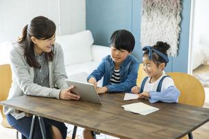 タブレットPCを見る日本人親子3人の写真素材 [FYI04087529]