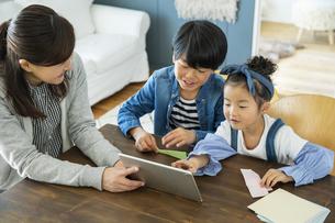 タブレットPCを見る日本人親子3人の写真素材 [FYI04087530]