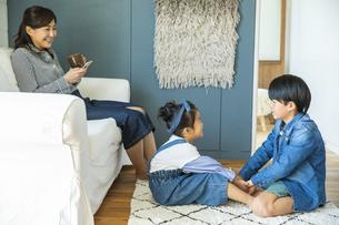 リビングでくつろぐ日本人親子3人の写真素材 [FYI04087536]