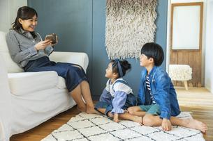 リビングでくつろぐ日本人親子3人の写真素材 [FYI04087537]