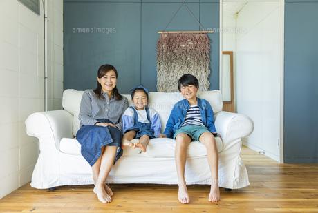 ソファーに座る笑顔の日本人親子3人の写真素材 [FYI04087538]