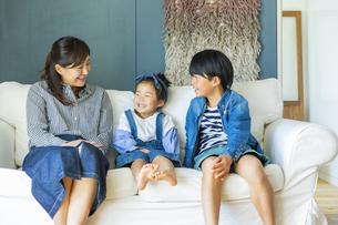 ソファーに座る笑顔の日本人親子3人の写真素材 [FYI04087539]