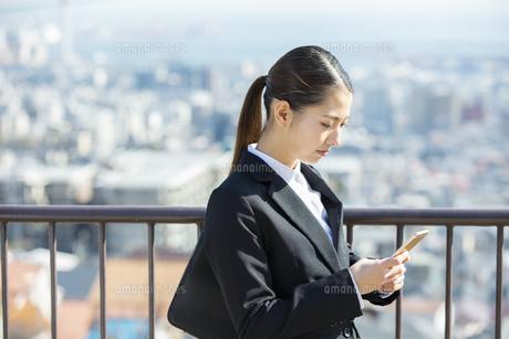 スマートフォンを見る日本人ビジネス女性の写真素材 [FYI04087546]