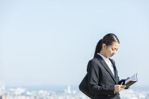 スケジュールを確認する日本人ビジネス女性の写真素材 [FYI04087549]