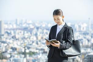スケジュールを確認する日本人ビジネス女性の写真素材 [FYI04087551]