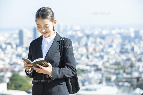 スケジュールを確認する日本人ビジネス女性の写真素材 [FYI04087554]