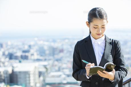 スケジュールを確認する日本人ビジネス女性の写真素材 [FYI04087555]