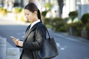スマートフォンを見る日本人ビジネス女性の写真素材 [FYI04087563]