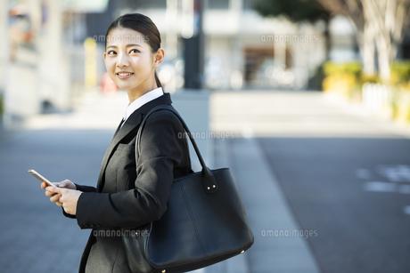 スマートフォンを持つ日本人ビジネス女性の写真素材 [FYI04087564]