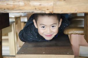 机の下からのぞいている男の子の写真素材 [FYI04088056]