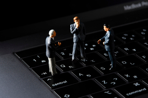 キーボードの上で会議するビジネスマンの写真素材 [FYI04088172]