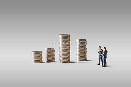 積みあがったお金とビジネスマンの写真素材 [FYI04088180]