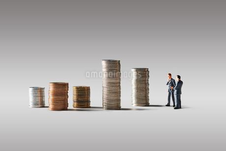 積みあがったお金とビジネスマンの写真素材 [FYI04088181]