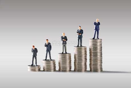 お金の上に並ぶビジネスマンの写真素材 [FYI04088187]