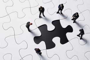 パズルのピースを見つめるビジネスマンの写真素材 [FYI04088202]