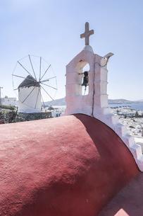 赤い屋根の教会の鐘と十字架越しにアノ・ミリの丘の風車を見る風景の写真素材 [FYI04088233]