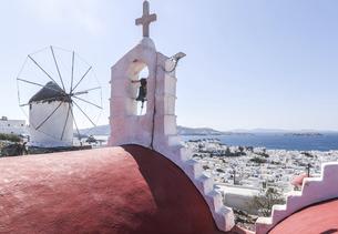教会の鐘と十字架とアノ・ミリの丘の風車越しに見下ろすエーゲ海とミコノスタウンの写真素材 [FYI04088234]