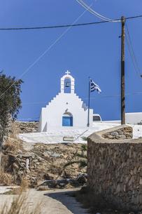 ミコノス島白い教会と国旗がなびく風景の写真素材 [FYI04088251]