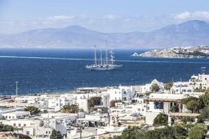 ミコノスタウン越しにエーゲ海に浮かぶヨットを見る風景の写真素材 [FYI04088258]