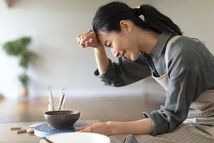 陶芸をしながら汗を拭う女性の写真素材 [FYI04088399]