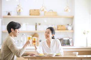 食事しながらビールを飲む夫婦の写真素材 [FYI04088401]