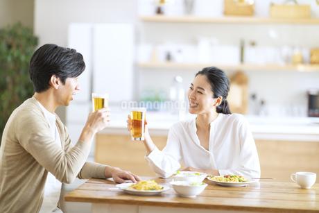 食事しながらビールを飲む夫婦の写真素材 [FYI04088402]