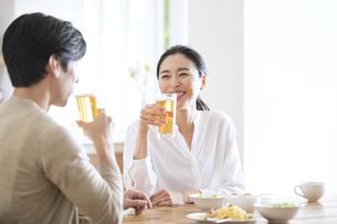 食事しながらビールを飲む夫婦の写真素材 [FYI04088403]