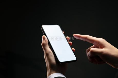 スマートフォンを操作するビジネスマンの写真素材 [FYI04088832]