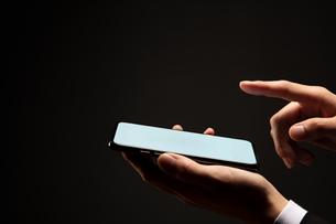 スマートフォンを操作するビジネスマンの写真素材 [FYI04088840]