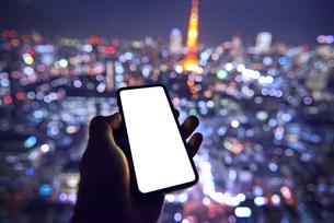 東京を背景にスマートフォンを持つ人の写真素材 [FYI04088854]
