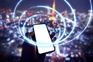 東京を背景にスマートフォンを持つ人の写真素材 [FYI04088856]