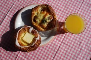皿の上の総菜パンとオレンジジュースの写真素材 [FYI04088936]