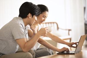 部屋でノートパソコンをしながら会話する夫婦の写真素材 [FYI04089047]