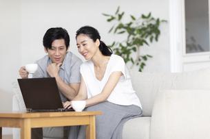 部屋でノートパソコンをしながら会話する夫婦の写真素材 [FYI04089048]
