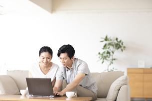 部屋でノートパソコンをしながら会話する夫婦の写真素材 [FYI04089049]