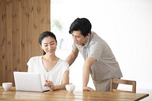 部屋でノートパソコンをしながら会話する夫婦の写真素材 [FYI04089050]