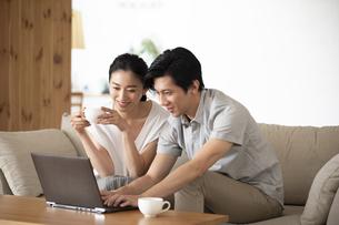部屋でノートパソコンをしながら会話する夫婦の写真素材 [FYI04089052]