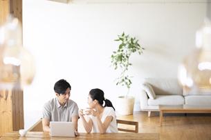 部屋でノートパソコンをしながら会話する夫婦の写真素材 [FYI04089054]