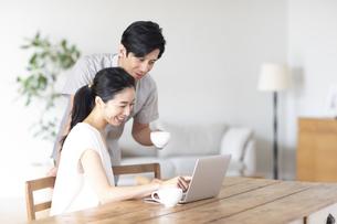 部屋でノートパソコンをしながら会話する夫婦の写真素材 [FYI04089055]
